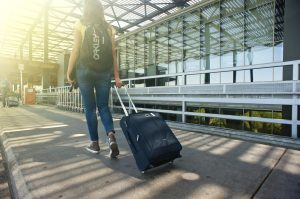 girl carrying a suitcase and a backpack